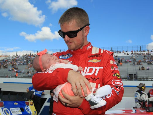 Justin Allgaier holds his daughter Harper Grace prior to the 5-Hour Energy 200 at Dover International Speedway on Sept. 28, 2013.