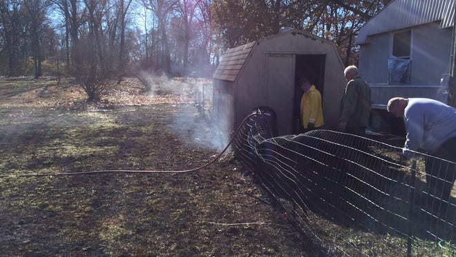 Burned grass and a smoldering shed are pictured from a CR 643 fire caused by burning trash in high winds on Friday.
