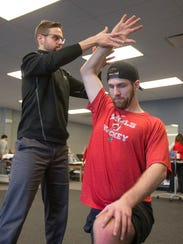 Greg Moore (left) of ATI Physical Therapy gently lifts