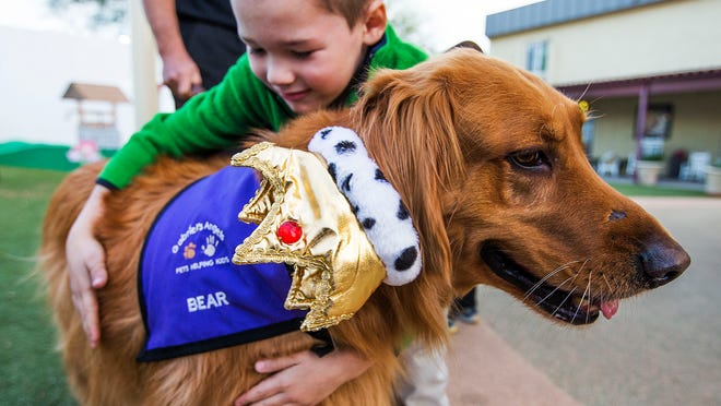 Bear, a 6-year-old golden retriever with Gabriel's Angels, gets a hug from fellow 6-year-old Carson during a visit to the UMOM shelter Thursday. Bear's jaunty crown was to celebrate his mother Codi's recent 10th birthday.