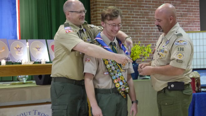 Joshua Brown, center, receives his Eagle Scout neckerchief from Boy Scout leaders Dana Harriger, left, and Jon Baughman.