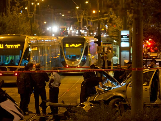 Israeli police officers inspect a car at the scene of an attack in Jerusalem, Wednesday, Oct. 22, 2014. A Palestinian motorist with a history of anti-Israel violence slammed his car into a crowded train station in Jerusalem on Wednesday, killing a three-month-old baby girl and wounding several people in what police called a terror attack.
