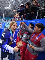U.S. forward Brianna Decker, of Dousman, Wis., celebrates with fans after defeating Canada in the women's ice hockey gold medal match.