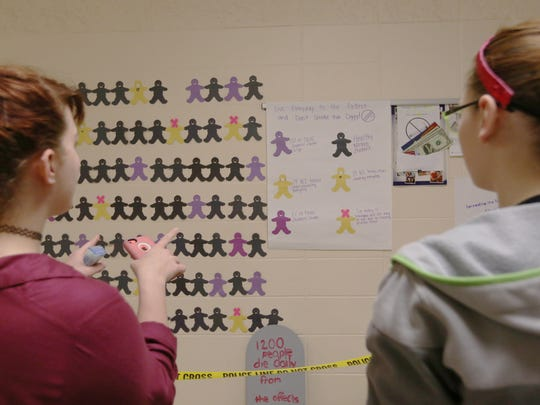 "Two Rivers High School seniors Baylee Krogh, 17, and Michelle Sheahan, 18, look at a ""paper people"" display in the school's hallway Wednesday, March 16. The paper people represent the number of TRHS students who smoke. According to the Kick Butts campaign, 13 percent of TRHS students smoke e-cigarettes and 11 percent smoke cigarettes."