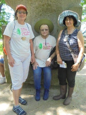 June Gebhardt, Judy Widman and Mary Lee Minor stopped to experience amplified sounds of nature and Lake Erie during their week at Nature Study Retreat. Here they are pictured atone of the sandstone blocks within Strock Memorial inLakeshore Reservation.