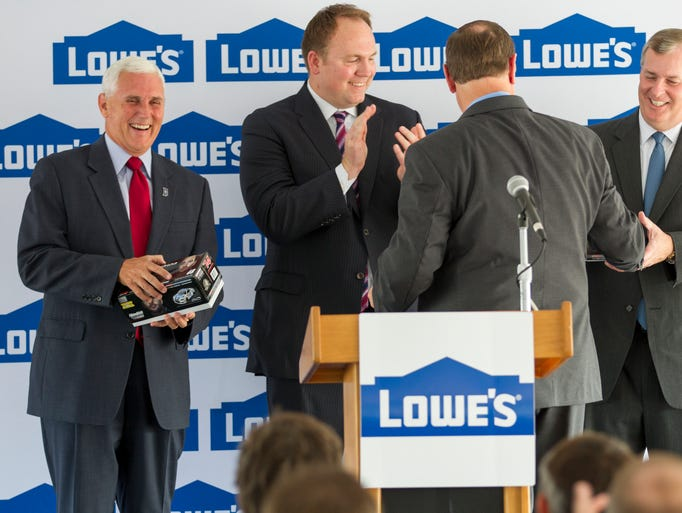 Don Easterling, Vice President of the Contact Center at Lowe's, presents Indianapolis Greg Ballard (right), and Governor Mike Pence (left), with autographed Jimmy Johnson NASCAR replica cars, as the city's Deputy Mayor for Economic Development, Deron Kintner, looks on, at a presentation to announce that Lowe's is bringing about 1,000 new jobs to the city via a call center on the city's northwest side, Tuesday, July 22, 2014.