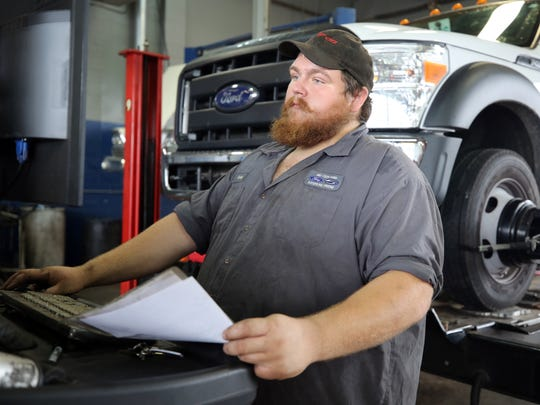 Cody McNeil operates a computer alignment system while