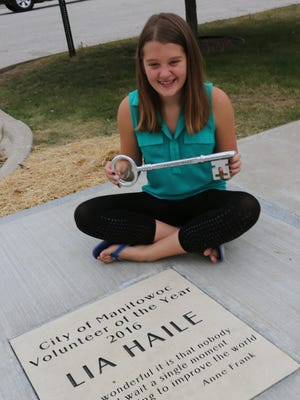"""Lia hold the Key to the City and sits next to her block on the Volunteer Walk of Fame. The quote reads: """"How wonderful it is that nobody need wait a single moment before starting to improve the world."""" -Anne Frank"""