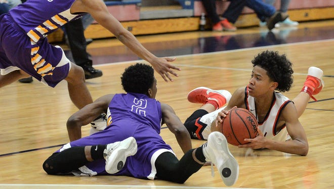 Oakland's Jaden Jamison grabs a loose ball as Columbia's Cameron Harvey (10) and Khalil Smith (2) scramble for the ball.