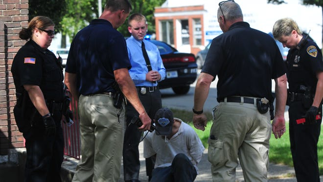 Richmond Police Department officers and detectives speak with Jonathan McClellan after he was arrested inside a north-side apartment building.