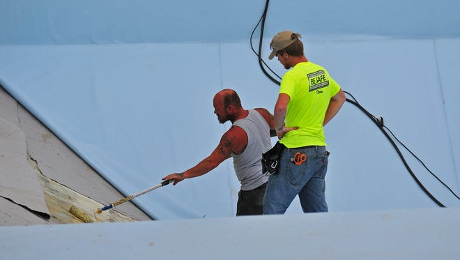 Dave Stone (left) and Daniel Rowe of Renosys work Friday to install the new liner in the diving well of Cordell Municipal Pool in Richmond.