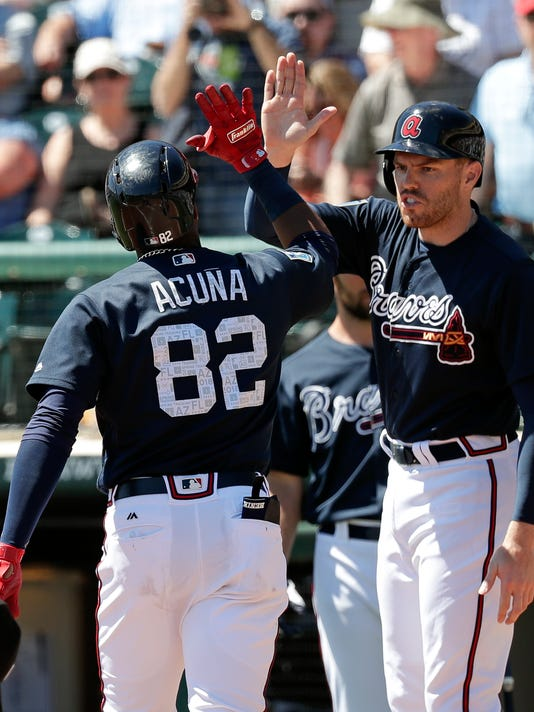 Atlanta Braves' Ronald Acuna Jr. (82) gets high five from Freddie Freeman, right, after hitting a home run in the third inning of a spring baseball exhibition game, Thursday, March 15, 2018, in Kissimmee, Fla. (AP Photo/John Raoux)