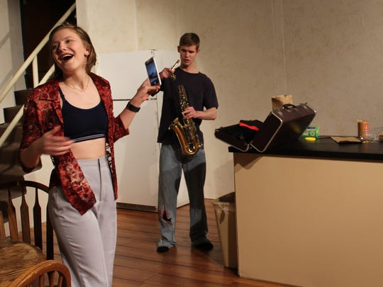 "Robert Taylor Jr. is a bit perplexed with the gift of a saxophone that prompts mom (Emily Hatch) to record on her phone in this rehearsal scene in ""From Up Here,"" the new Hardin-Simmons University theater production."