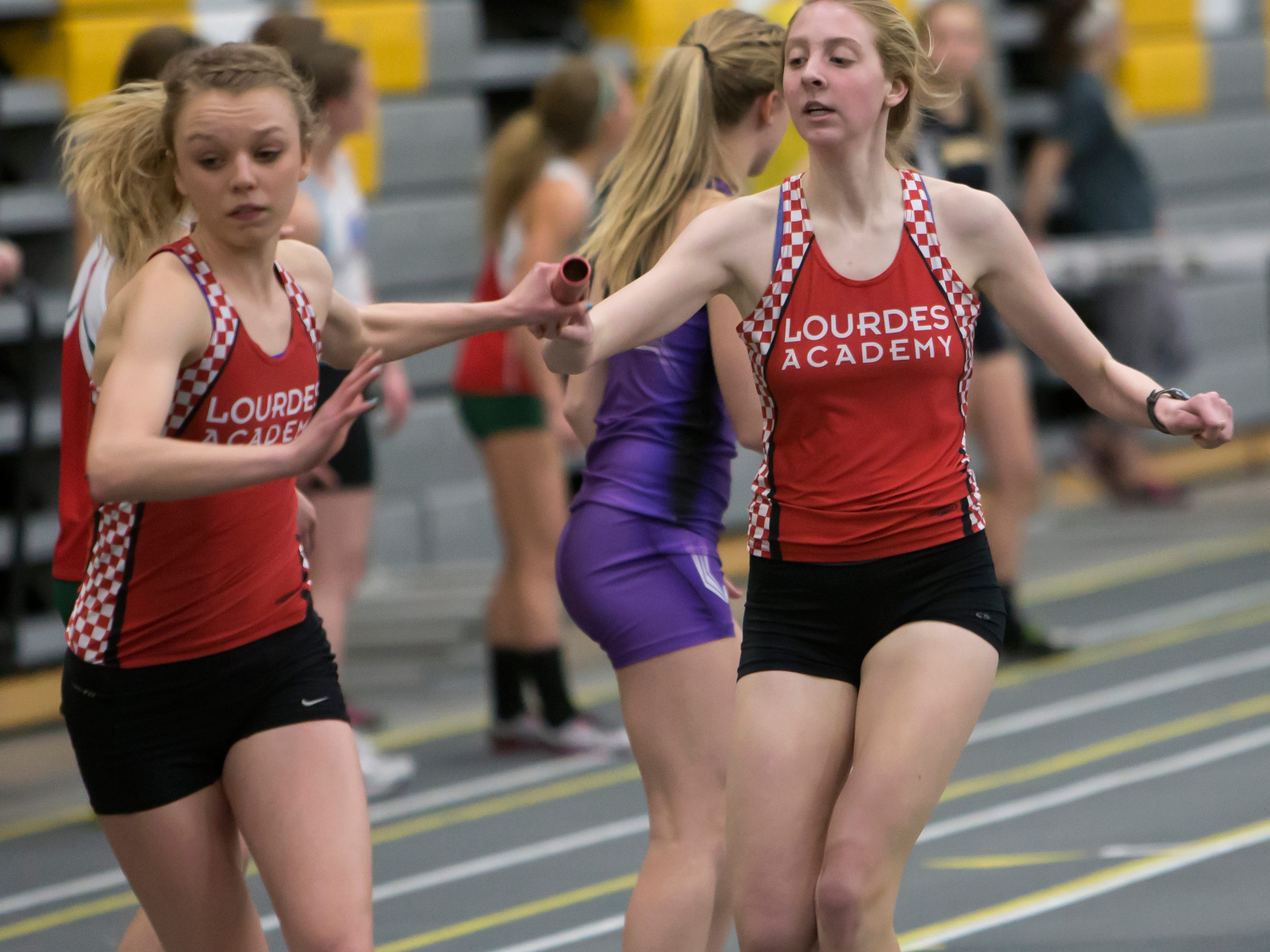 Lourdes' Nora Keller hands off the baton to Angela Moore in a meet Tuesday night at UW-Oshkosh.