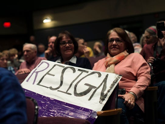 "A sign reading ""RESIGN"" sits in the audience during"