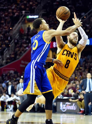 Cleveland Cavaliers guard Matthew Dellavedova (8) shoots the ball against Golden State Warriors guard Stephen Curry (30) during the fourth quarter in game three of the NBA Finals at Quicken Loans Arena.