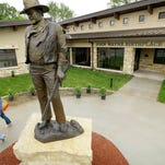 Tourists walk past a statue of John Wayne outside the John Wayne Museum in Winterset, Iowa. On May 23, Winterset will help launch the official opening of the newly built museum celebrating Wayne's life and career.