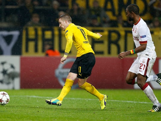 Dortmund's Marco Reus, left, scores his side's opening goal during the Champions League group D soccer match between Borussia Dortmund and Galatasaray Istanbul in Dortmund, Germany, Tuesday, Nov.4, 2014. (AP Photo/Frank Augstein)