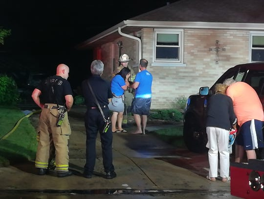 The distraught owners of the home speak to firefighters