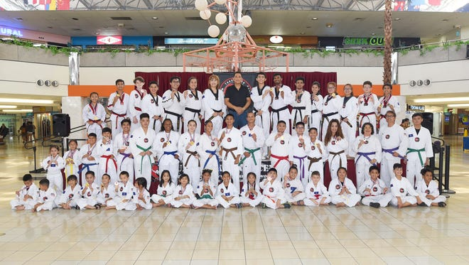 Master Noly Caluag, chief instructor of Guam Taekwondo Center and organizer of the games is seen in the back row center with the medalists and the blackbelt demonstration team during the closing ceremonies of the 6th Taekwondo Poomsae & 3rd Weapons Tournament at the Micronesia mall last Sunday.