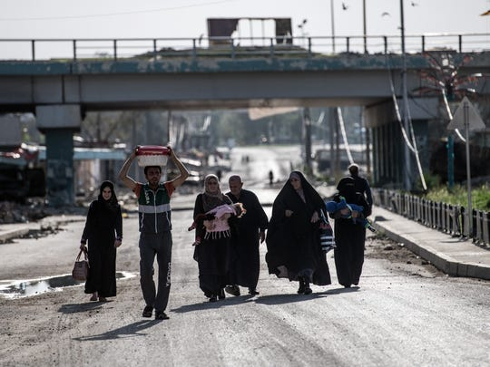 Iraqis carry their possessions as they leave an area
