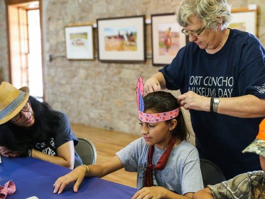 Volunteer Linda Weaver puts a headdress on Zoie  Clark