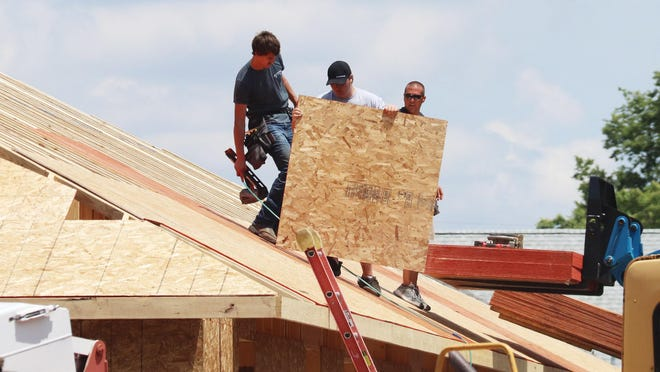 Employees of Meister Wood and Finish of Ashkum work to complete the shell of a house on Water Street Monday afternoon.