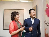 Matue couple holding wine glass, smiling