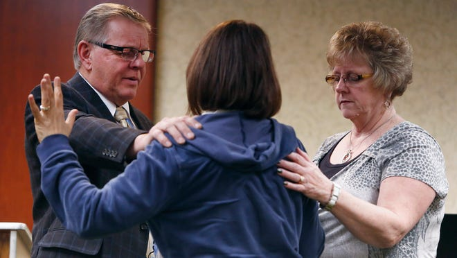 The Rev. Tom Rouse and wife Renee (right) pray with a member of the congregation during a service Sunday at the La Quinta Inn Oak Room in Grand Chute.
