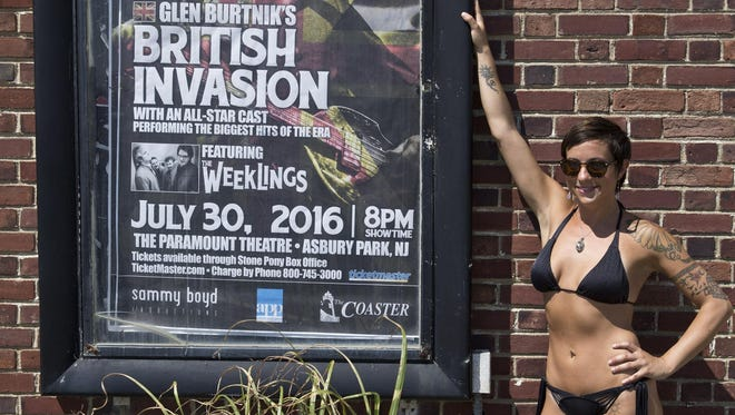 Brittany James of Asbury Park poses with a Glen Burtnik's British Invasion poster on the south side of Convention Hall. James recently posted a similar picture on social media which many others have duplicated. Asbury Park, NJ Wednesday, July 20, 2016