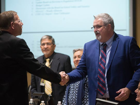 Las Cruces Public Schools Superintendent Greg Ewing shakes hands with Damien Willis, who was introduced as the new head of communications for the school district during the Tuesday April 17, 2018 school board meeting.