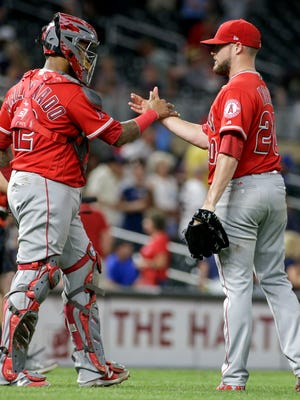 Los Angeles Angels relief pitcher Bud Norris (20) is congratulated by Martin Maldonado (12) after the Angeles defeated the Minnesota Twins 2-1 in a baseball game, Wednesday, July 5, 2017, in Minneapolis.