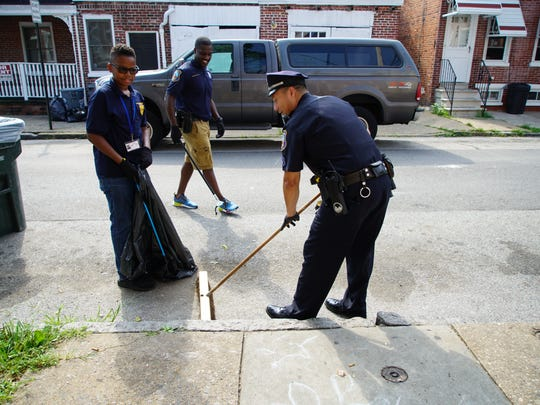 Officers with the Wilmington police cleanup the streets with a Wilmington Police Department Youth Academy participant.