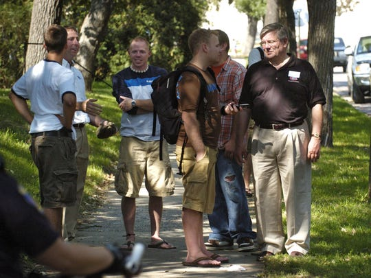 St. Cloud State University President Earl H. Potter III (right) and St. Cloud Mayor Dave Kleis (back, left) talk to students in the neighborhood near campus