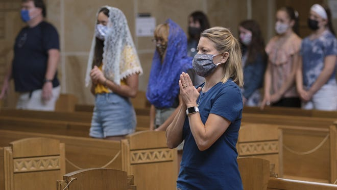 Mary Vautour, 52, of Eastmoor wears a mask as she prays during Mass at St. Catharine Catholic Church on th East Side on Wednesday, May 27, 2020. Until this week, Ohio's Catholic churches had opted to stay closed for in-person Mass since mid-March due to coronavirus concerns.