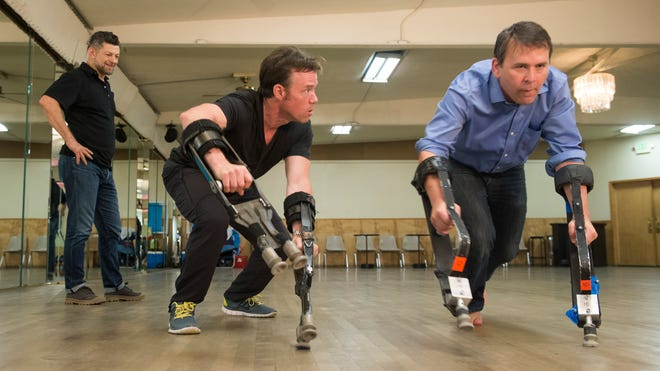 "Actor Andy Serkis, left, looks on as Terry Notary gives USA TODAY's Bryan Alexander lessons on how to walk like a primate. Serkis stars as Caesar, the leader in the new film ""Dawn of the Planet of the Apes,"" and Notary is Rocket. Notary was also the movement choreographer and stunt coordinator for the film."