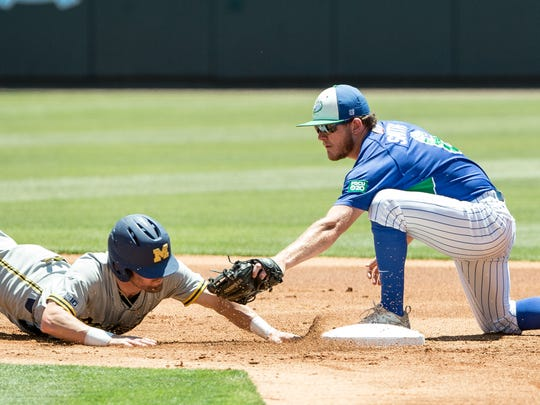 Michigan's Michael Brdar, left, slides safely back into second base under the tag of Florida Gulf Coast's Jake Smith, right during an NCAA regional baseball tournament game in Chapel Hill, N.C. on Friday, Jun. 2, 2017.
