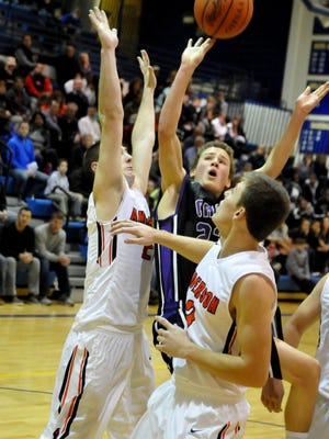 CHCA's Blake Southerland(23) powers a layup over the outstretched arms of Anderson's Jackson Long while Cody Shiver watches.