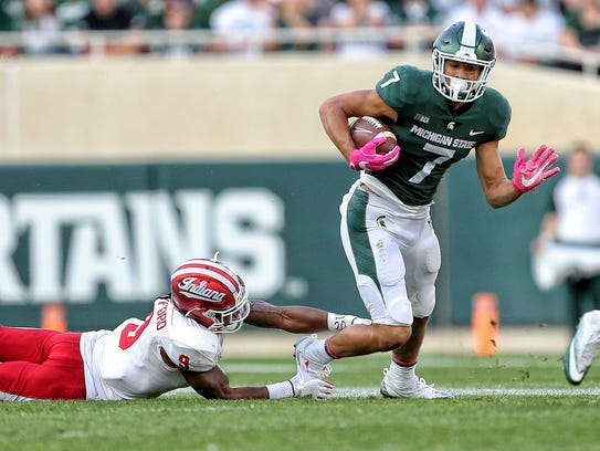 Michigan State's Cody White runs for yards after a catch against Indiana's Jonathan Crawford in the second half at Spartan Stadium on Oct. 21, 2017.