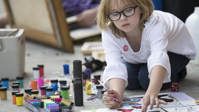 Elsie McNulty, 12, works on a painting at last year's Art Squared event in Fountain Square.