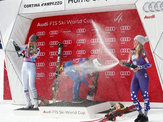 FILE - In this Friday, Jan.19, 2018 file photo, Italy's Sofia Goggia, center, winner of an alpine ski, women's World Cup downhill, celebrates on the podium with second-placed United States' Lindsey Vonn, left, and third-placed United States' Mikaela Shiffrin, in Cortina D'Ampezzo, Italy. Separated in age by about a decade, Lindsey Vonn and Mikaela Shiffrin head to the Pyeongchang Olympics as the past, present and future of ski racing in the United States and around the world.(AP Photo/Alessandro Trovati, File)