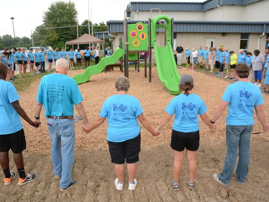 "Dan and Jeanie Smith (foreground) join hands with volunteers at the dedication of the Elizabeth ""Betsy"" Smith Playground in Marion."