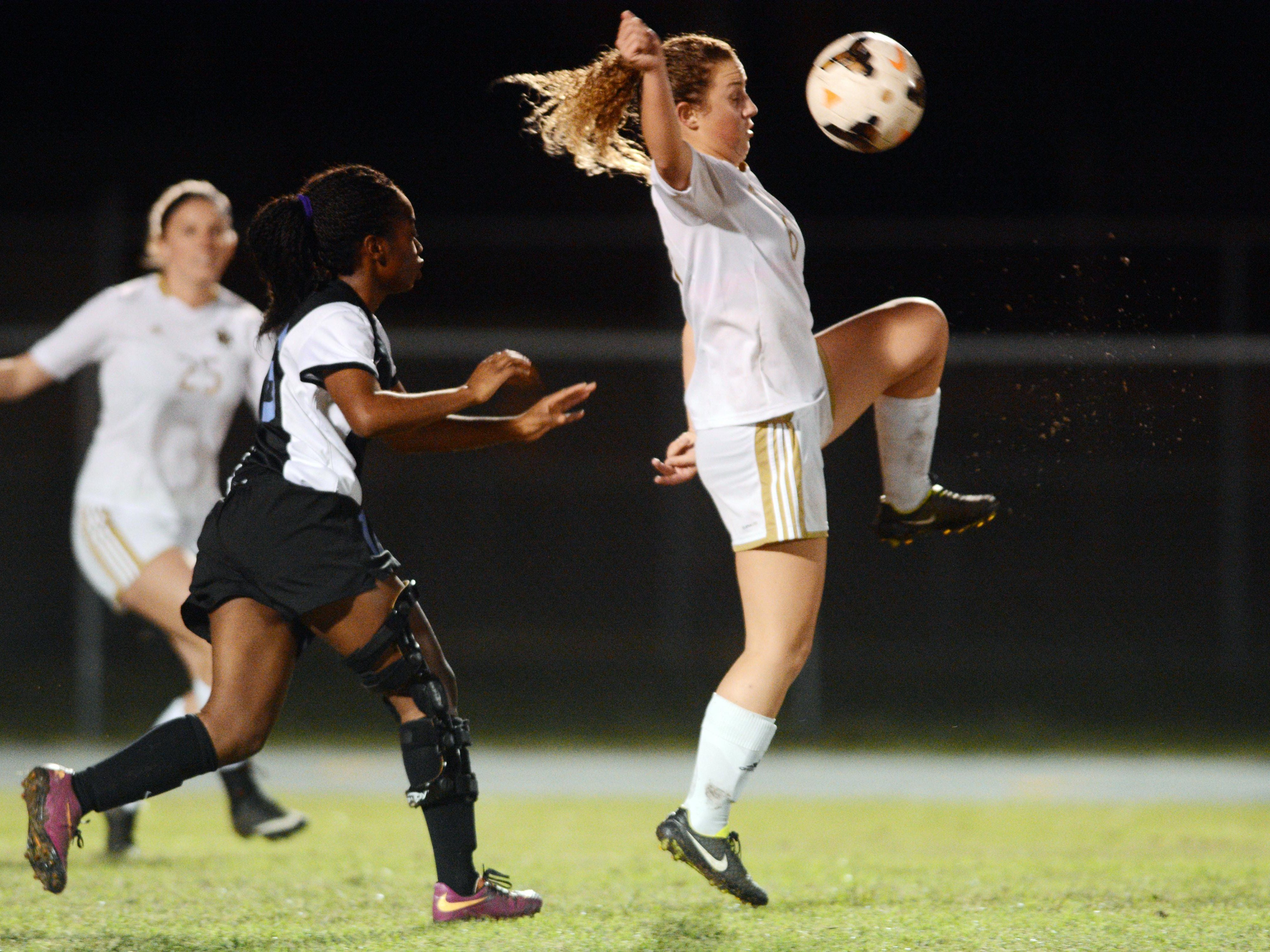 Merritt Island's Julia Martin (right) settles the ball in front of Rockledge player Cierra Cadore during their district championship game Friday evening.