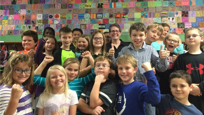 """Students at Rosenow Elementary School are learning how to have """"grit"""" this school year. They recently completed an art project on sandpaper with local artist-in-residence Mel Kolstad (back row, center)."""
