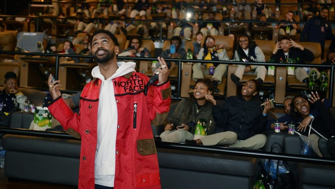 """Big Sean looks up to the big screen after talking to students before the showing of """"Black Panther."""""""