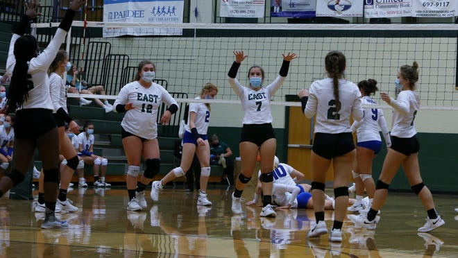 East Henderson's Molly Gilliam (7) celebrates with her teammates after getting a point against Brevard during Monday's season opener at East.