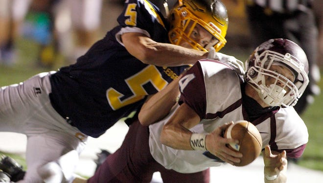 Okemos' Brandon Clark, right, drives for the goal line against Grand Ledge's Nate Eckhardt, Friday, Sept. 22, 2017, in Grand Ledge, Mich. Clark was short but Okemos scored on a subsequent play. Grand Ledge won 28-20.