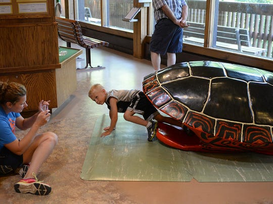 A large replica tortoise shell kids can crawl through draws the attention of visitors in the main level of the Nature Center at Bay Beach Wildlife Sanctuary on Thursday, July 9, 2015. Kristin Gagnon, left, waits for her son Isaac to exit during a day outing at the center.