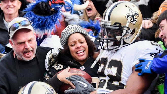 After scoring a touchdown New Orleans Saints running back Mark Ingram (22) jumps into the stands and gives the ball to a Saints fan.