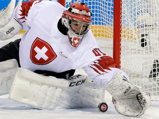 goalie Florence Schelling (41), of Switzerland, reaches for the puck during the third period of the preliminary round of the women's hockey game against Sweden at the 2018 Winter Olympics in Gangneung, South Korea, Wednesday, Feb. 14, 2018. (AP Photo/Matt Slocum)